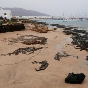 Au Sud de Caleta de Sebo, sable et roche volcanique noire.